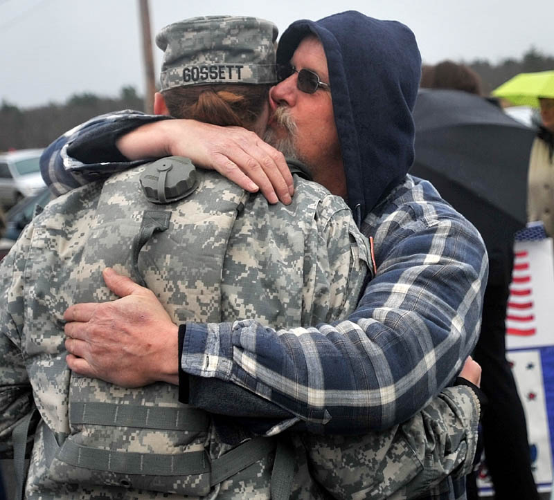 Staff photo by Michael G. Seamans Timothy Grenier, right, hugs and kisses Rita Gossett, after a Veteran's Day ceremony at the Winslow Memorial Park Friday.