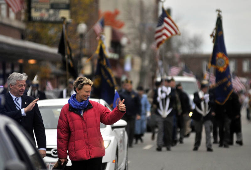 Staff photo by Michael G. Seamans Rep. Mike Michaud, left, and mayor-elect Karen Heck, wave to people on Main Street in Waterville during the Veteran's Day parade.