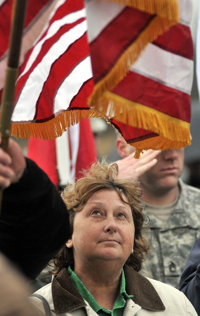 Staff photo by Michael G. Seamans Lorna Raymond watches the American flag during the playing of TAPs during a Veteran's Day ceremony at Memorial Park in Winslow Friday.