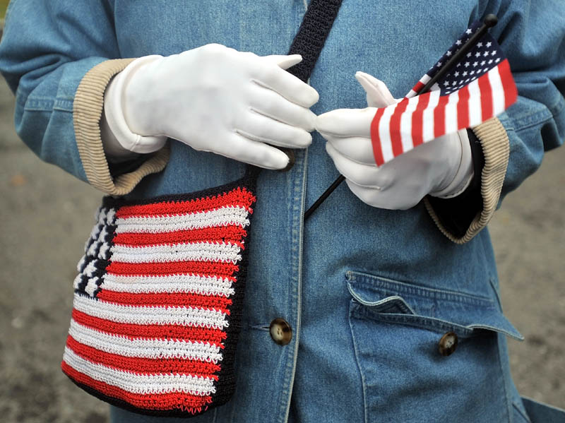 Staff photo by Michael G. Seamans Marie McMahon holds a small flag along with her American flag embroidered bag before the start of the Veteran's Day parade at Head of Falls in Waterville Friday morning.