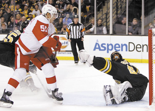 OPENING GOAL: Detroit's Valtteri Filppula, left, scores on Bruins goalie Tuukka Rask during the first period Friday in Boston. Rask made 29 saves but gave up two goals in three shootout chances.