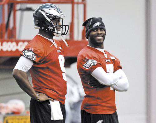 WHO'S IT GONNA BE? Philadelphia Eagles quarterback Vince Young, left, stands as quarterback Michael Vick smiles during an indoor practice Wednesday in Philadelphia. The Eagles have not said whether Young or Vick will start today against the Patriots.