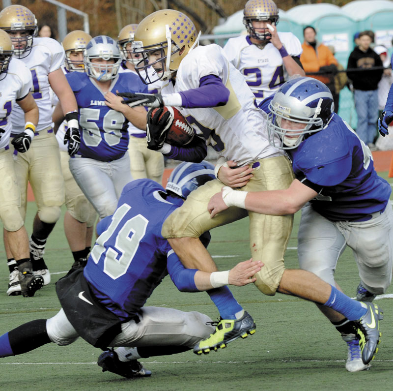 ON THE MOVE: Cheverus receiver Louie DiStasio runs is hit by Lawrence defenders Alex Leathers, left, and Luke Lawrence, right, during the Class A state championship game Saturday at Fitzpatrick Stadium in Portland. DiStasio caught four passes for 130 yards in the Stags' 49-7 win over Lawrence.