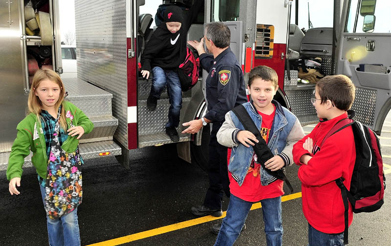 NICE RIDE; Skowhegan firefighter Rick Caldwell helps Bloomfield Academy students from left, Olivia Dunbar, Jeremiah Emery, Clay Porter and Damion Scanlin exit a firetruck after riding to school in the truck on Tuesday. Children in the school district wrote a fire safety checklist as part of Fire Prevention week, according to Caldwell. The kids names were picked in a raffle for the unique ride to school.