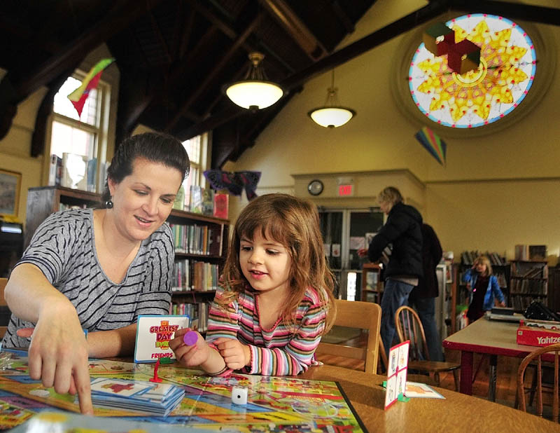 Laura Closson and her four-year-old daughter Kya Closson play a game in the Gardiner Public Library children's room on Saturday morning.