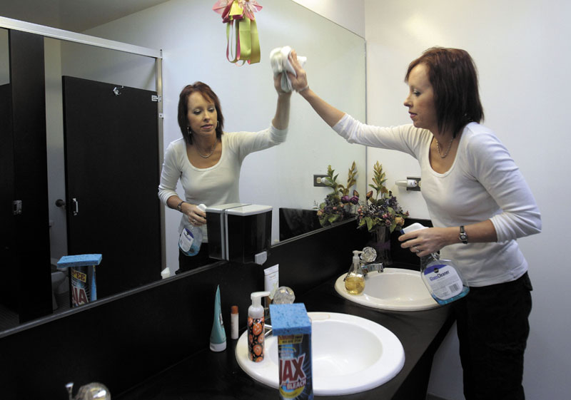 Michelle Hartman, an elementary school teacher, cleans a mirror at an accounting firm in Oakland Park, Fla. The single mother has a master's degree in educational leadership and has been a teacher 15 years. But she says she cannot afford to leave any of her additional jobs. The extra jobs bring in about $6,000 more a year salary on top of her $46,000 a year salary.