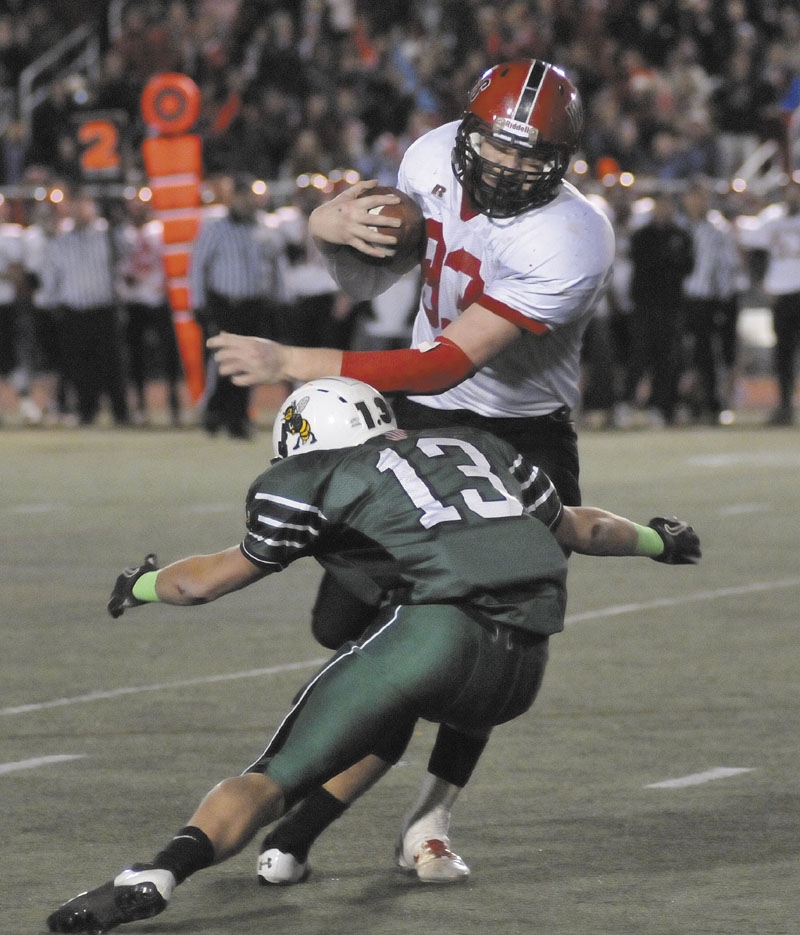 NOT GOING DOWN EASILY: Joshua Ingalls, right, of Wells tries to elude the tackle of Leavitt's Brian Bedard during the Class B state championship football game Saturday in Portland.