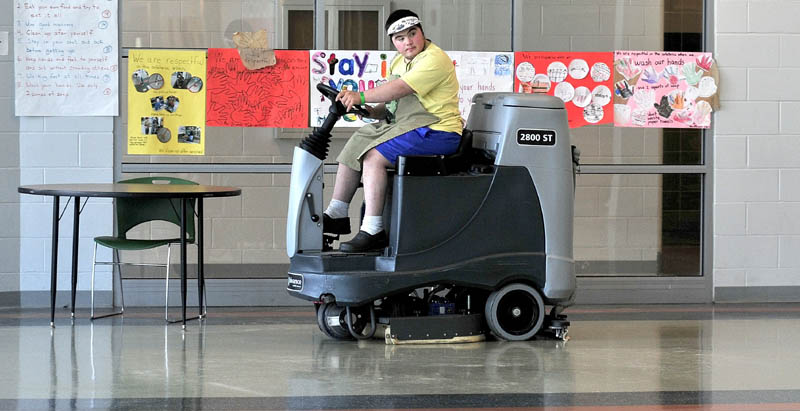 OPPORTUNITY: Mario Montana of Troy operates a riding floor cleaning machine recently in one of the cafeterias at Mount View High School in Thorndike. Montana, 19, has dealt with the challenges of being born with Down syndrome. He graduated last June and is now employed by Regional School Unit 3.