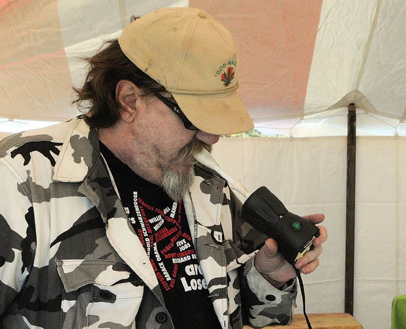 VAPORIZER AT WORK: Chris Kenoyer uses a Happy Vappy vaporizer to inhale marijuana in a tent in the parking lot during the Medical Marijuana Caregivers' Home Grown Maine trade show Saturday at the Augusta Civic Center.