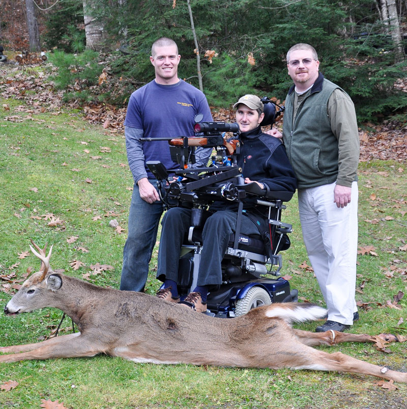 Jeff Molloy, center, poses with a 118-pound four-point buck he shot on Nov. 12 in Albion. With the help of friends Elisha Fowlie, left, and Will Rood, Molloy used a self-designed adaptive shooting system to bag his first deer since a 2004 accident that left him paralyzed from below the chest.