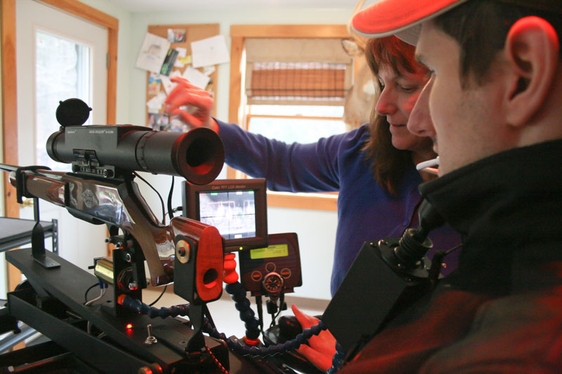 Christine Saban, left, helps her son, Jeff Molloy, attach an adaptive shooting device to his wheelchair Sunday at their Palermo home. Molloy and his friend, machinist Ray Kimball, designed and built the device, called the Equalizer Shooting System. On Nov. 12 in Albion, Molloy used the system to bag a 118-pound four-point buck.