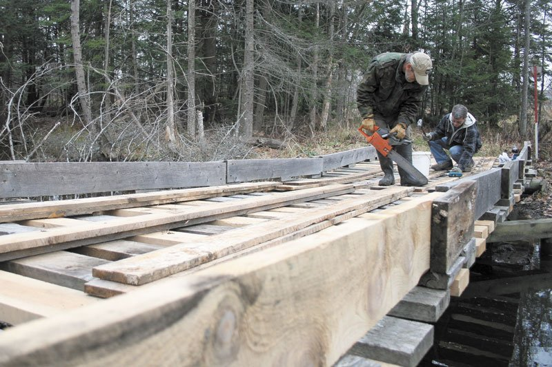 FIXING THINGS UP: Robert Bickford, left, cuts boards while Eric Roberts drives nails on a snowmobile bridge Sunday in Waterville. Due to a shortage of volunteers, the two men perform all of the yearly maintenance for Central Maine Snowmobile Club's trail system. Many of Maine's 287 snowmobile clubs have difficulty finding volunteers to maintain the state's 14,000-mile trail system.