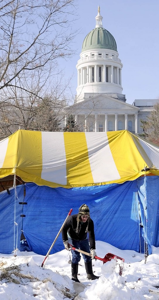 PREOCCUPIED: Jenny Gray, of Wiscasset, shovels snow onto a tarp in the Occupy Augusta encampment Friday morning in Augusta's Capitol Park. She and several other people were clearing snow piles from the area.
