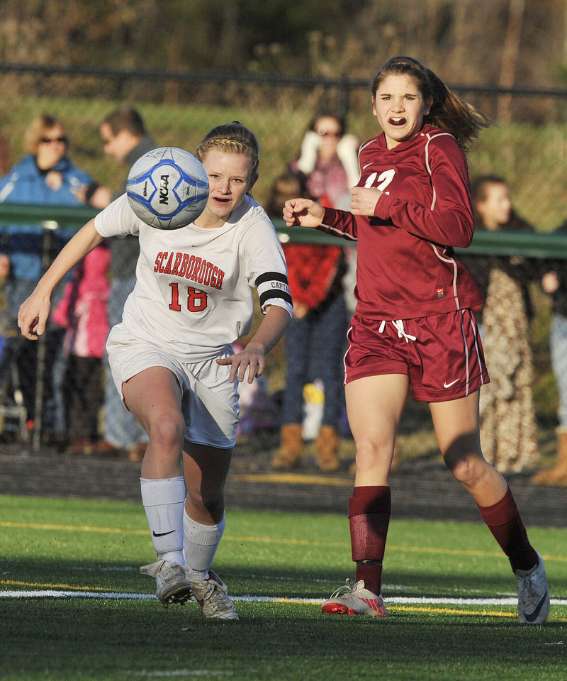 John Ewing/Staff Photographer Haley Carignan, left, of Scarborough sends a shot toward the goal Saturday after slipping past Allison Vanidestine of Bangor in the Class A state final. Bangor won, 4-0.