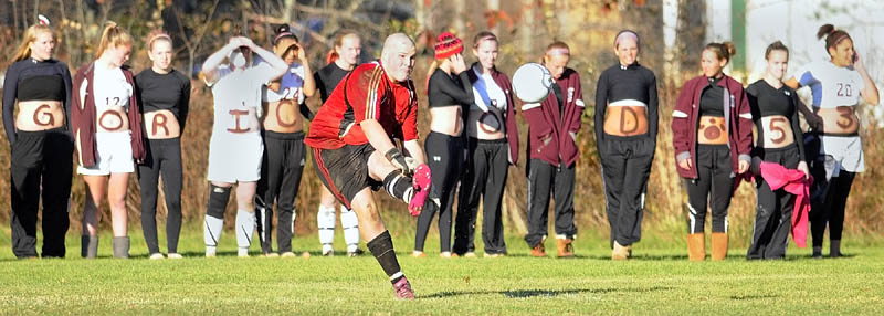 SHOW OF SUPPORT: Richmond goalkeeper Tyler Harrington kicks the ball during the Western Maine Class D championship game Wednesday in Richmond as members of the Bobcats girls team, who painted their stomachs for the occasion, cheer on the boys after winning their playoff game.