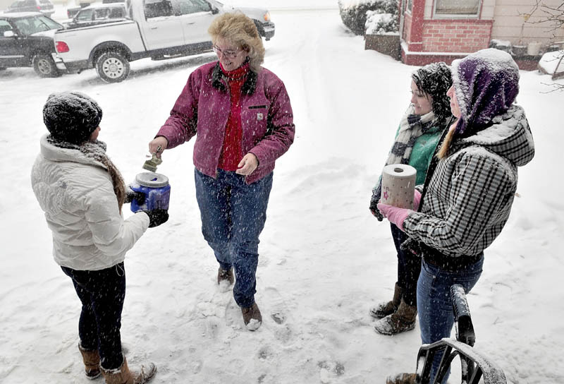 SNOW DANCE: The cold and snow on Wednesday didn't stop members of the Dance Connection dance team from seeking donations outside of Hamlin's Bakery in Fairfield. Laura Kent contributes to dancers Ali Tozier, left, Taylor Bouchard and Tricia Hasson.