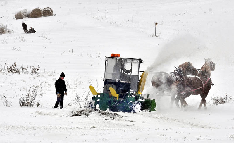SNOW WORK: Amish farmer Andrew Stoll guides his horses as they pull a diesel snowblower while clearing a road in Unity on Saturday. His son Raymond watches the progress as other kids are pulled on a sled.