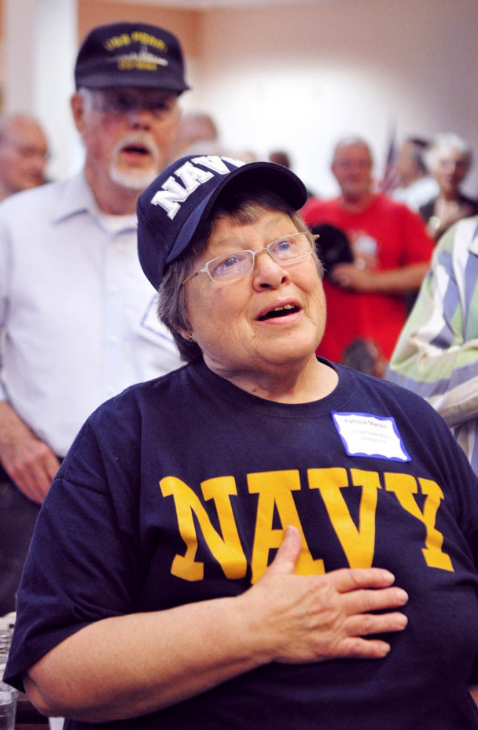 SALUTING THOSE WHO SERVED: Navy veterans Patricia Marvin, of East Winthrop, front, and Richard Duncan, of Augusta, sing the national anthem during the Veterans Day lunch Thursday at the Cohen Center in Hallowell. The center served a total of 230 lunches, 97 of them to veterans, according to center coordinator Maggie Tardiff. There were 19 World War II veterans, 29 from the Korean War and 31 from the Vietnam War, she added. The veterans' lunch featured ham, seafood newburg, mashed potatoes, vegetables, soup, salad and dessert. It was free for veterans and cost $5 for others.