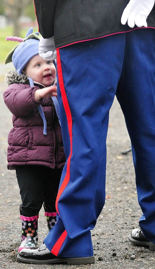 Lily Snyder toddles over to greet her father Marine Staff Sgt. Brice R. Snyder during Veterans Day ceremony in the Hallowell city cemetery Friday morning. Snyder was a guest speaker at the event that featured singing of patriotic songs and placing a wreath.