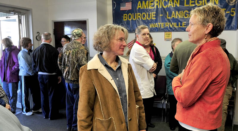MEET AND GREET: Waterville mayoral candidate Karen Heck, right, speaks with Jill Godfrey prior to polls opening at the American Legion in Waterville on Tuesday. Voters waited in a line that extended outside.