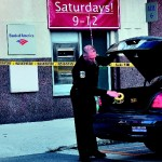 Waterville police officer Tim Hinton finishes taping off the front and rear of the Bank of America on Main Street in Waterville after a male entered the bank on Monday with a suspicious bag and left with an undetermined amount of money. The man was arrested nearby on suspicion of robbery.