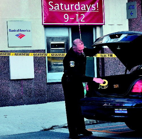Waterville police officer Tim Hinton finishes taping off the front and rear of the Bank of America on Main Street in Waterville after a male entered the bank on Monday with a suspicious bag and left with an undetermined amount of money. A man was arrested nearby on suspicion of robbery.
