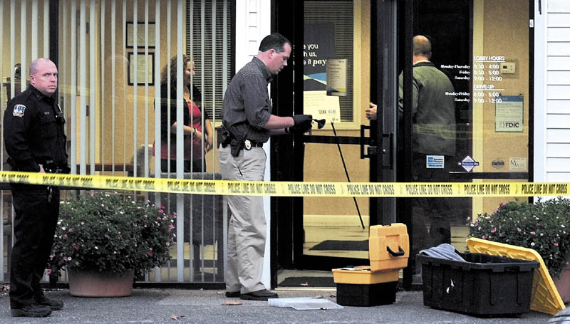 ANOTHER ROBBERY: Waterville police Detective David Caron dusts the door of the Waterville Savings Bank of Maine for fingerprints shortly after a reported armed robbery on Wednesday at the Upper Main Street bank. Officer Dennis Picard is at left and more police and employees were inside. It is the second bank robbery in 48- hours in Waterville.