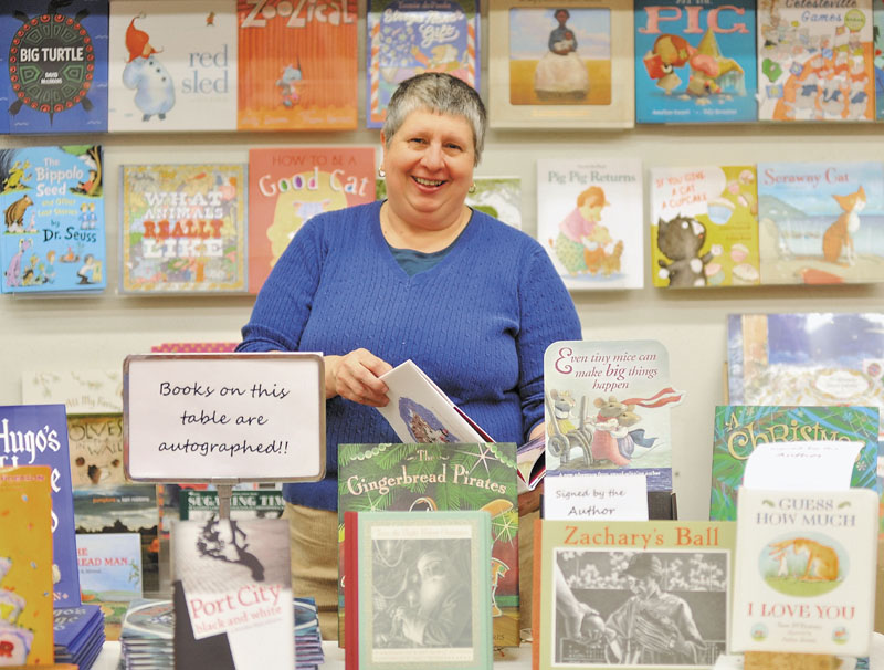 Ellen Richmond, owner of Children's Book Cellar at 52 Main St. in Waterville, organizes merchandise for holiday shoppers on Thursday.