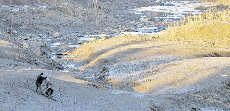 STILL LOOKING: A searcher scours the emptied river bed of the Messalonskee Stream along West River Road near the intersection of Kennedy Memorial Drive in Waterville Tuesday afternoon for Ayla Reynolds.