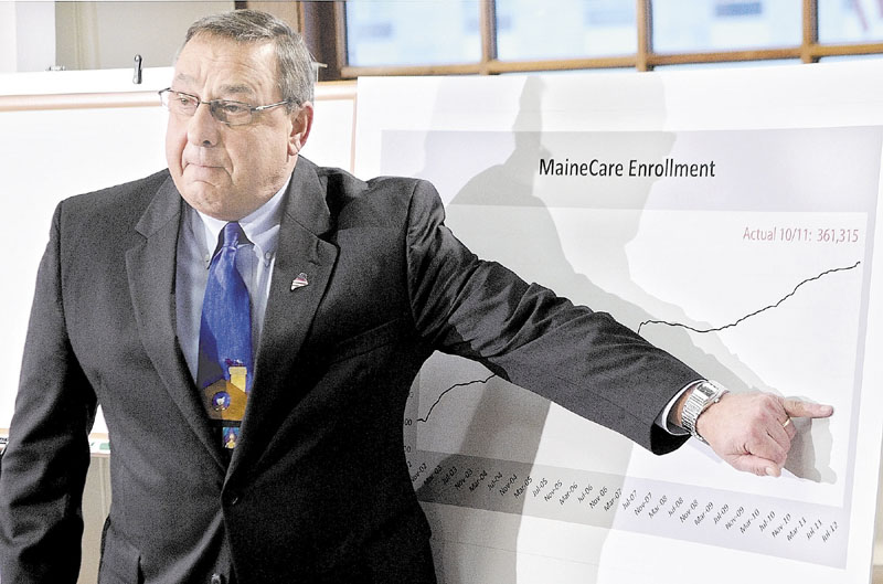 DOLLARS AND CENTS: Gov. Paul LePage gestures at graph to show how much lower he'd like to see MaineCare enrollment numbers drop at a news conference last week in Augusta. Lawmakers will take up the governor's proposal this week.
