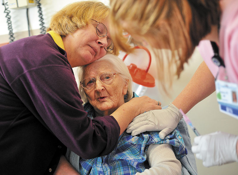 CARE: Cheryl Barkow comforts her mother Alice Osborne as she receives a flu shot from a nurse during a visit to the doctor at Franklin County Memorial Hospital in Farmington last week. Osborne, 93, has dementia.