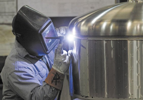 WORKING: Kevin Offield makes a weld on a tank earlier this month at JV Northwest, a manufacturer in Canby, Ore. Jobless claims fell to the lowest level since the spring of 2008, the Labor Department said Thursday.