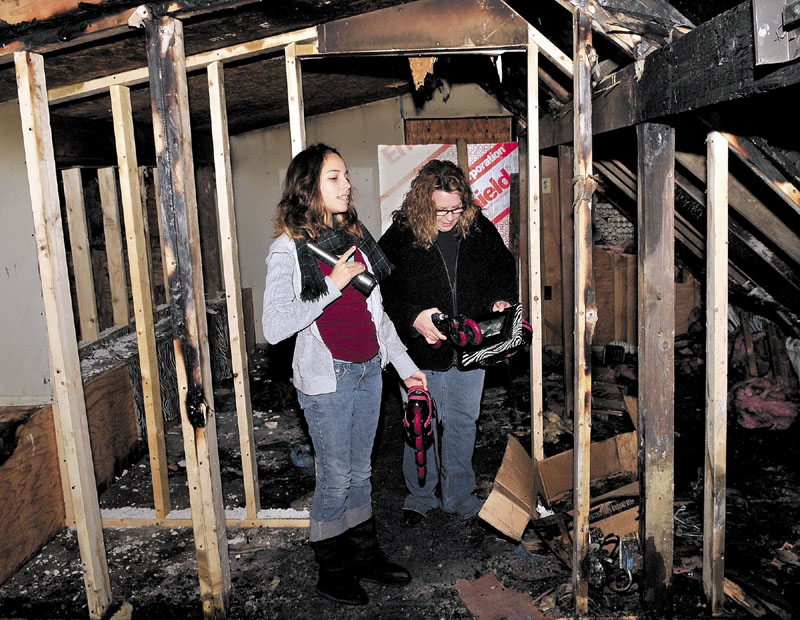 SEARCHING: Lori Fisher, right, and her daughter Adriana on Thursday search for salvageable items in Adriana's bedroom at an apartment building they lived in that was seriously damaged by fire earlier this week in Anson.