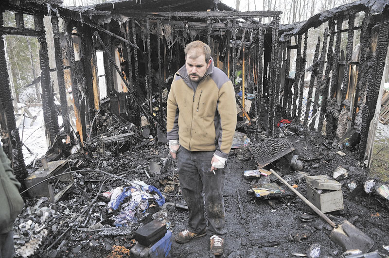 FIRE IN OAKLAND: Ryan Shuman stands in what used to be the living room of his family's mobile home after a fire there early Tuesday morning in Oakland. Shuman barely made it out of the home alive and was taken by LifeFlight helicopter to a hospital in Bangor, where he was later released with burns to his hands, feet and back. On Tuesday afternoon, Shuman was using his bandages hands to salvage anything that wasn't destroyed.