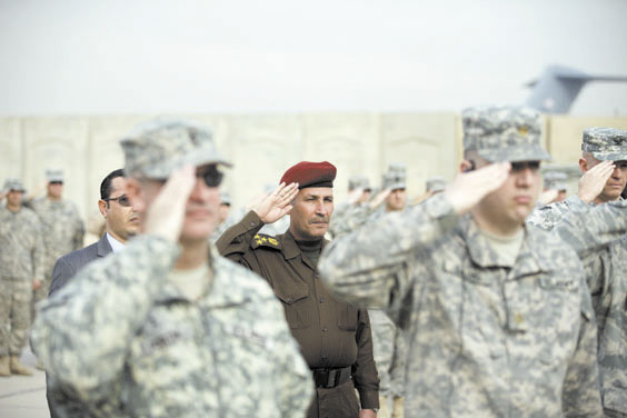 LEAVING: An Iraqi officer, center, and U.S. Army soldiers salute during ceremonies marking the end of the U.S. military mission in Baghdad on Thursday. After nearly nine years, 4,500 American dead, 32,000 wounded and more than $800 billion spent, U.S. officials formally shut down the war in Iraq a conflict that U.S. Defense Secretary Leon Panetta said was worth the price in blood and money, as it set Iraq on a path to democracy.