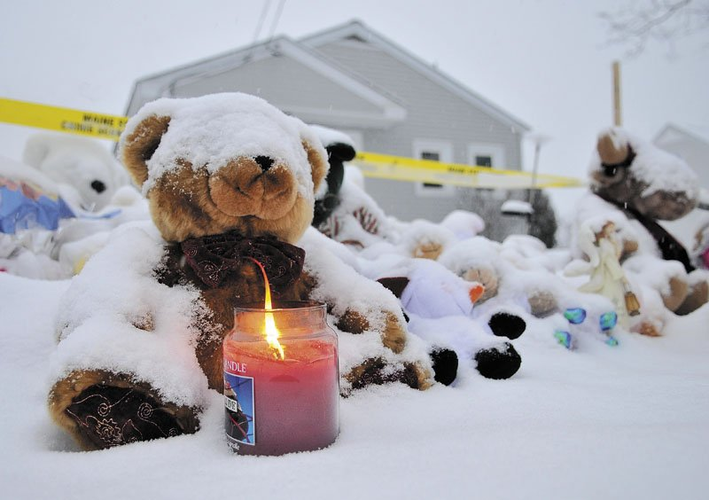 WAITING: A candle illuminates a growing teddy bear shrine for missing girl Ayla Reynolds outside her home in Waterville on Sunday.