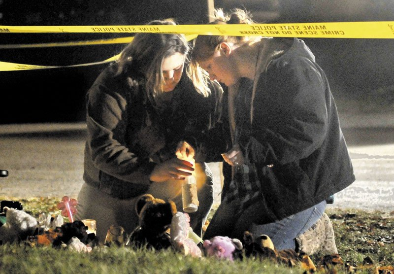 Heather Mirucki, left, and Ashley Tenney, right, light candles at a teddy bear shrine in front of the home of missing girl Ayla Reynolds on Violette Avenue in Waterville on Thursday night.