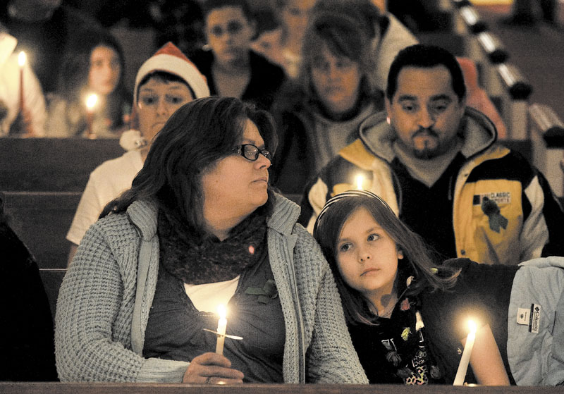 LIGHTS: Katherine McIntyre, left, sits with her daughter Noelle, 7, at a vigil for Ayla Reynolds organized by the Mainely Moms & Dads organization at the First Congregational Church in Waterville on Wednesday.