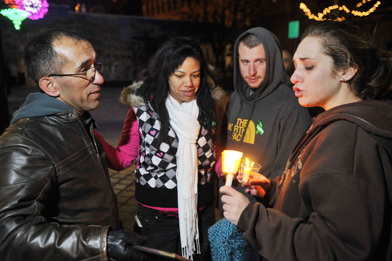 HOPING: Ayla Reynolds' mother Trista Reynolds, right, is consoled by her father, Ronald Reynolds, left, and her stepsister, Whitney Raynor of Portland, second from left, and her fiance, Charles Martin of Westbrook, at a vigil for the missing girl in Portland's Congress Square on Friday night.