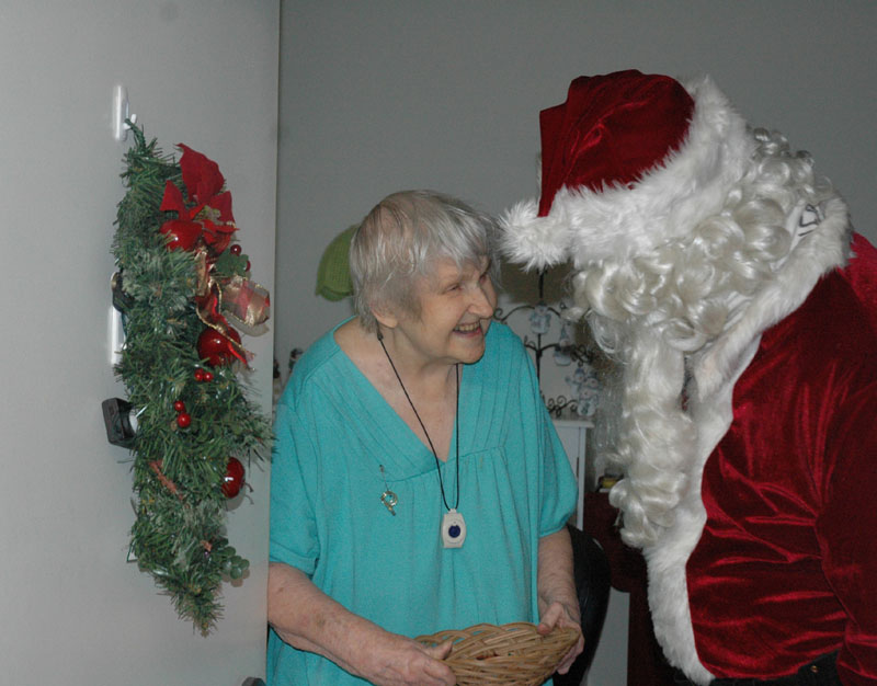 A VISIT FROM ST. NICK: Ann Figar, a resident of Fairmount Circle Drive in Norridgewock, greets Santa with a big smile on Saturday during Santa's annual pre-Christmas rounds. Firefighter James Gordon has donned the Santa suit to visit the town's older folks for 25 years.