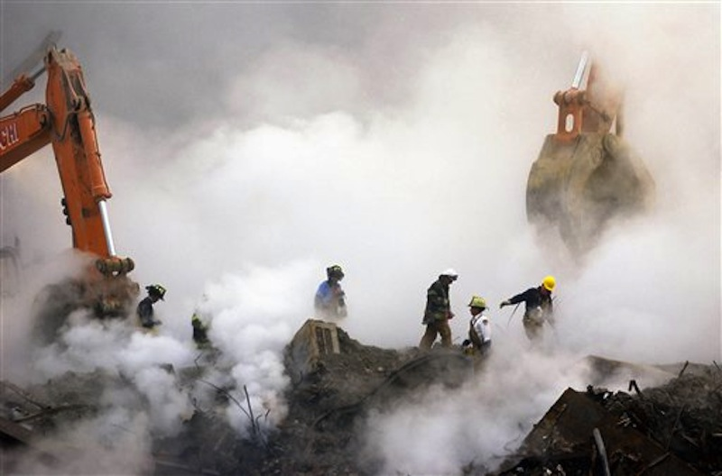 In this Oct. 11, 2001 file photo, firefighters make their way over the ruins of the World Trade Center through clouds of dust and smoke at ground zero in New York. More than 1,600 people suing over their exposure to World Trade Center dust must decide by Jan. 2 whether to keep fighting in court, or drop their lawsuits and apply for benefits from a government fund. (AP Photo/Stan Honda, Pool, File)