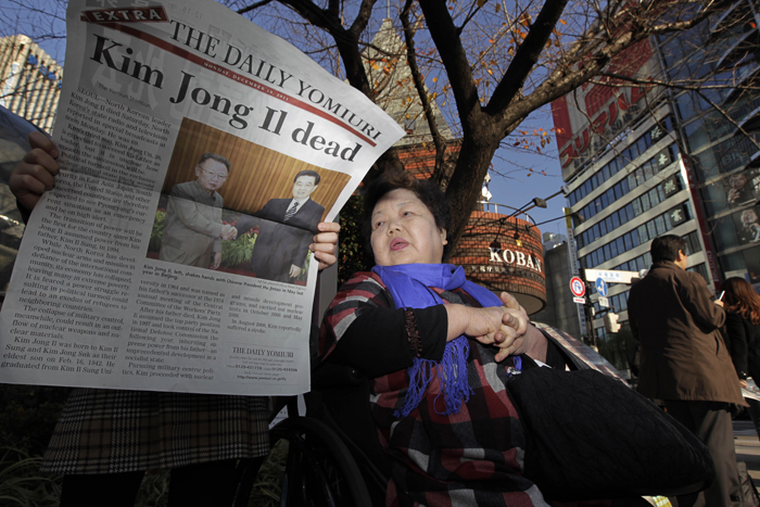 A woman reads an extra issue of a Japanese newspaper at Ginza district in Tokyo today.