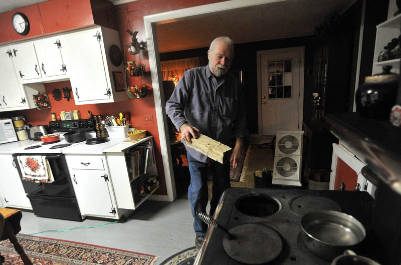 KEEPING WARM: Jay Adams places another log in the stove at home in Phillips on Thursday.