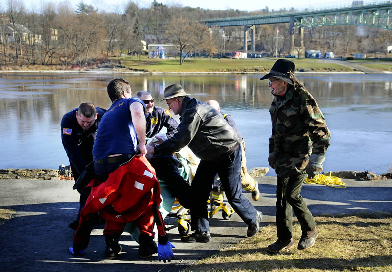 A man is pushed to an ambulance Tuesday morning after he jumped from the Calumet bridge and then was recovered from the Kennebec River in downtown Augusta. Kennebec County sheriff's deputies, Maine State Police and Augusta police assisted the Augusta Fire Department in bringing the man to shore.