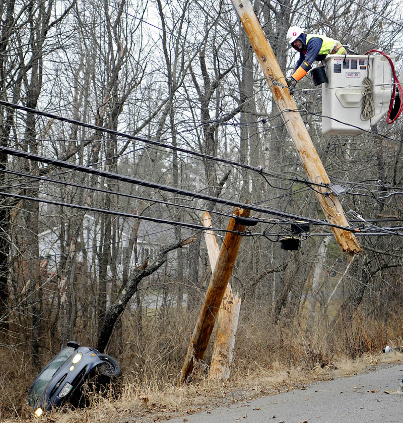 Central Maine Power lineman Ed Lake saws the top of a utility pole Wednesday morning after a car carrying two people snapped it, injuring both occupants, on the Churchill Road in Augusta. Several accidents were reported across Kennebec County due to black ice.