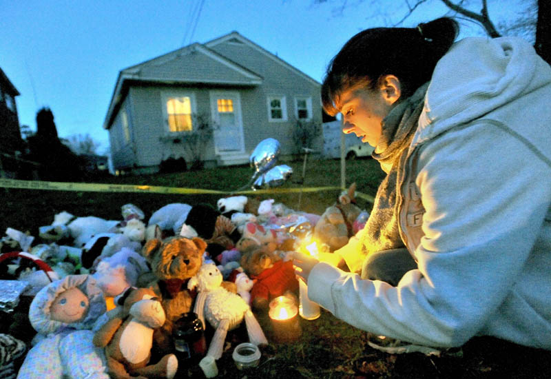 THINKING OF AYLA: Tara True, of Winslow, lights candles at the ever-growing teddy bear shrine for missing 20-month-old Ayla Reynolds in front of her home at 29 Violette Ave. in Waterville.