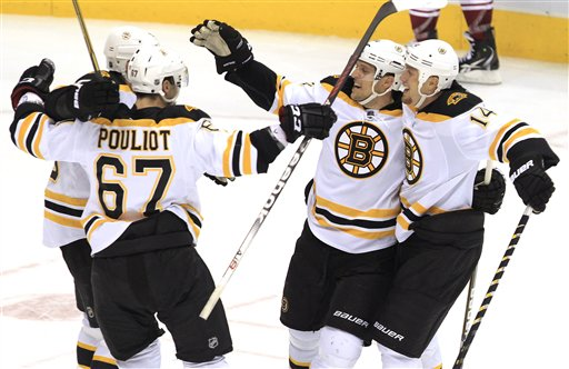 Boston Bruins' Joe Corvo (14), Benoit Pouliot (67) and Chris Kelly, back left, celebrate a game-winning goal scored by Dennis Seidenberg, second from right, during overtime Wednesday against the Phoenix Coyotes in Glendale, Ariz. The Bruins defeated the Coyotes 2-1.