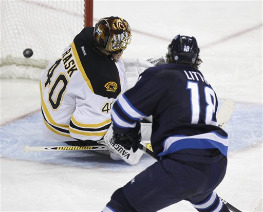 Winnipeg Jets' Bryan Little (18) puts the puck past Boston Bruins goaltender Tuukka Rask during the third period of an NHL hockey game in Winnipeg, Manitoba, on Tuesday. Canada Canadian sports play ice hockey game action competitive competition compete athletics athletic athlete NHL National Hockey League