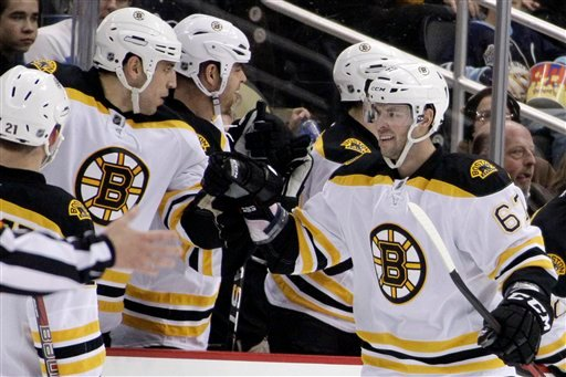 Boston Bruins' Benoit Pouliot (67) celebrates with teammates as he returns to the bench after scoring a second period goal past Pittsburgh Penguins goalie Marc-Andre Fleury on Monday in Pittsburgh.