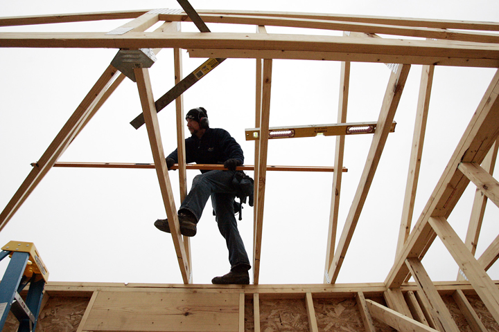 A worker sets a roof truss on a home under construction in LaPorte, Ind., recently.